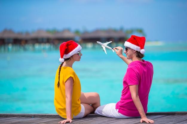 Giovani coppie in cappelli di santa che si rilassano sul molo di legno sulla vacanza di natale