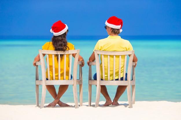 Giovani coppie in cappelli di santa che si rilassano sulla spiaggia tropicale durante le vacanze di natale