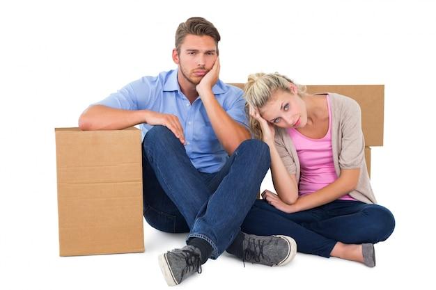 Giovani coppie infelici che si siedono accanto alle scatole commoventi