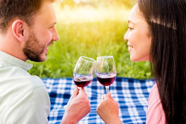 Giovani coppie innamorate multietniche che bevono vino rosso sul picnic