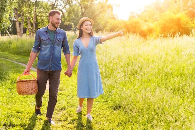Giovani coppie innamorate multietniche che camminano nel tenersi per mano del parco