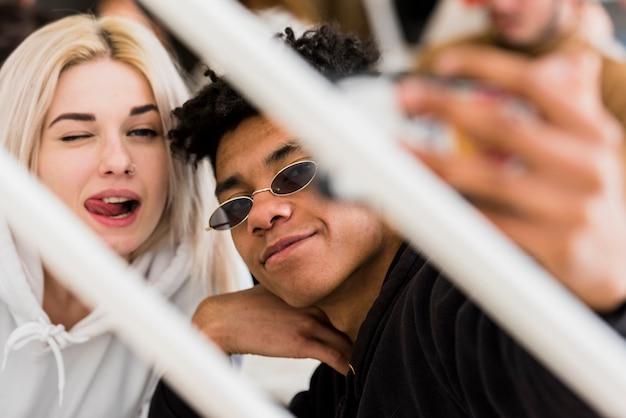 Giovani coppie interrazziali che prendono selfie sullo smartphone