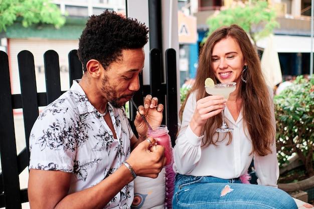 Giovani coppie interrazziali nell'amore che bevono un cocktail al bar di estate