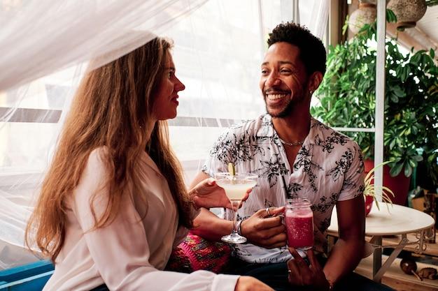 Giovani coppie interrazziali nell'amore che bevono un cocktail al bar