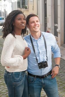 Giovani coppie interrazziali sorridenti facendo un giro turistico all'aperto
