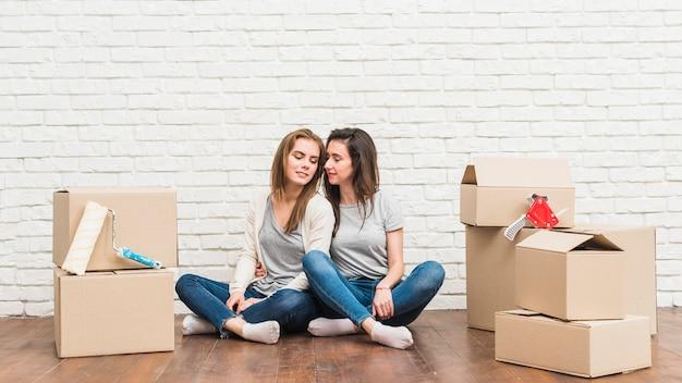 Giovani coppie lesbiche amorose che si siedono sul pavimento di legno duro con le scatole di cartone commoventi nella loro nuova casa