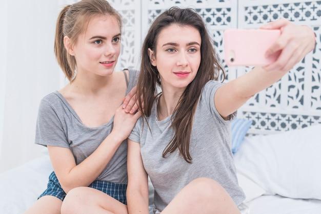 Giovani coppie lesbiche che si siedono sul letto che prende selfie sul telefono cellulare