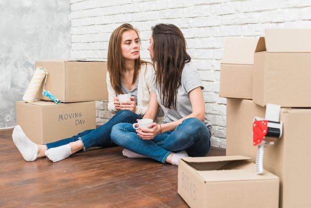 Giovani coppie lesbiche che tengono la tazza di caffè in mani che se lo esaminano che si siedono fra le scatole di cartone