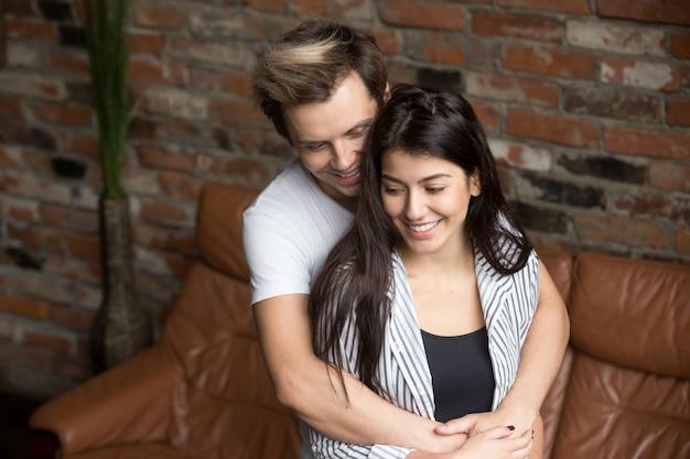Giovani coppie millenarie che si abbracciano a casa, felici della prima gravidanza