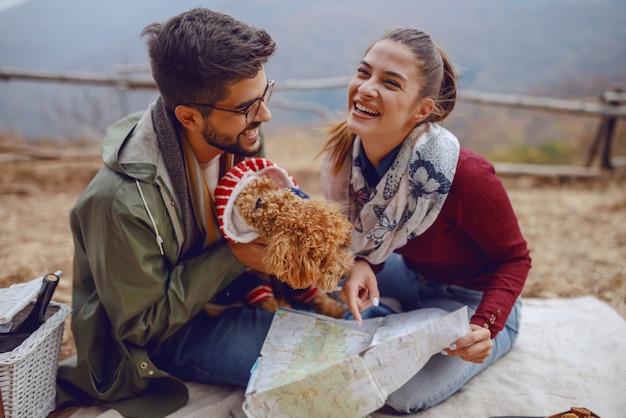 Giovani coppie multiculturali sveglie nell'amore che si siedono sulla coperta e che esaminano mappa.
