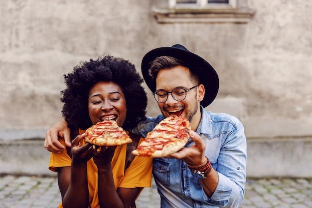 Giovani coppie multirazziali sveglie che si siedono all'aperto e che mangiano pizza.