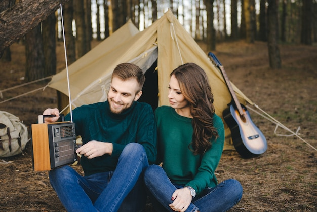 Giovani coppie nei turisti di campeggio di amore che si siedono da un fuoco contro una tenda nella foresta che ascolta la retro radio