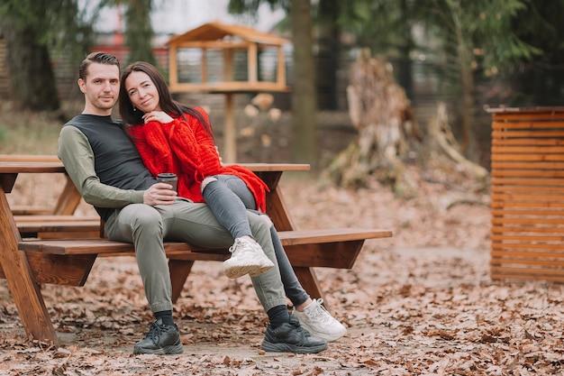 Giovani coppie nel parco all'aperto ad una tavola autentica in un caffè