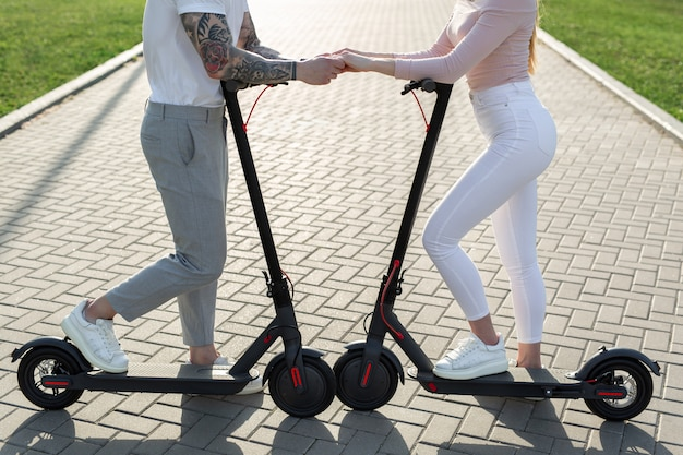 Giovani coppie nel parco sugli scooter elettrici