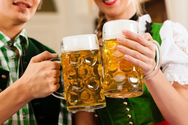 Giovani coppie nel tradizionale bavarese tracht in ristorante o pub