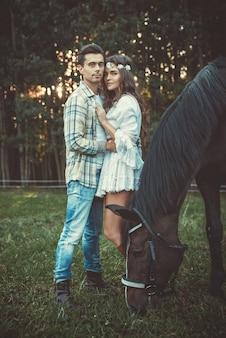 Giovani coppie nell'abbraccio sul prato con cavalli