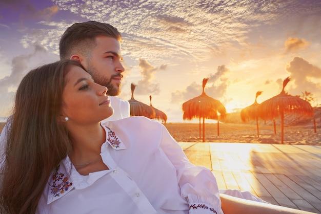Giovani coppie nell'alba di vacanza della spiaggia
