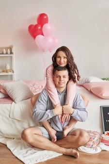 Giovani coppie nell'amore a casa sul letto che celebra san valentino