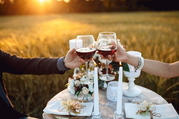 Giovani coppie nell'amore ad un appuntamento romantico con i vetri in mani dell'ir