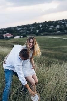 Giovani coppie nell'amore all'aperto. ritratto all'aperto sensuale sbalorditivo di giovane giovane posa alla moda alla moda durante l'estate nel campo