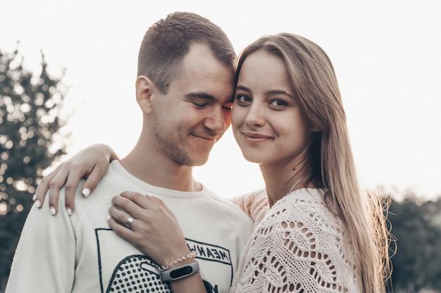 Giovani coppie nell'amore all'aperto. stanno sorridendo e si guardano l'un l'altro. chiuda sul ritratto di bellezza romantica delle coppie felici nell'amore abbracci e divertirsi, luce solare serale, colori solari, stile vintage.