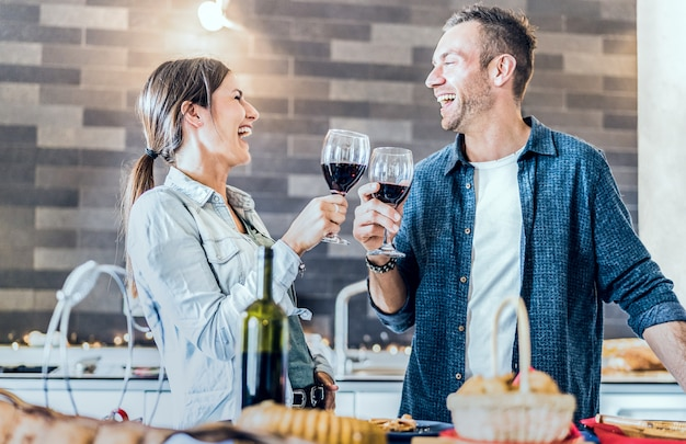 Giovani coppie nell'amore che beve vino rosso alla cucina della casa