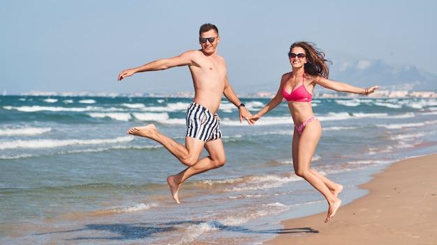 Giovani coppie nell'amore che cammina sulla spiaggia.