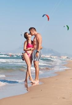 Giovani coppie nell'amore che ha momenti teneri romantici sulla spiaggia.