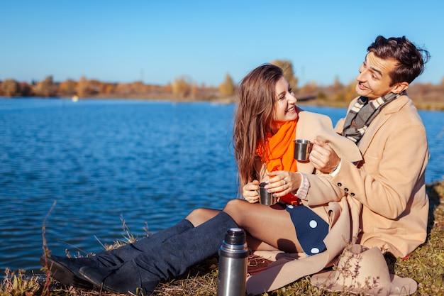 Giovani coppie nell'amore che ha picnic dal lago di autunno. uomo e donna felici che scherzano e che godono del tè