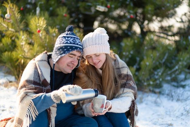 Giovani coppie nell'amore che si siede in inverno nella foresta