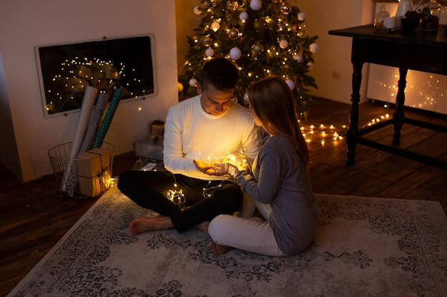 Giovani coppie nell'amore che si siedono davanti al camino e l'albero di natale piacevolmente decorato