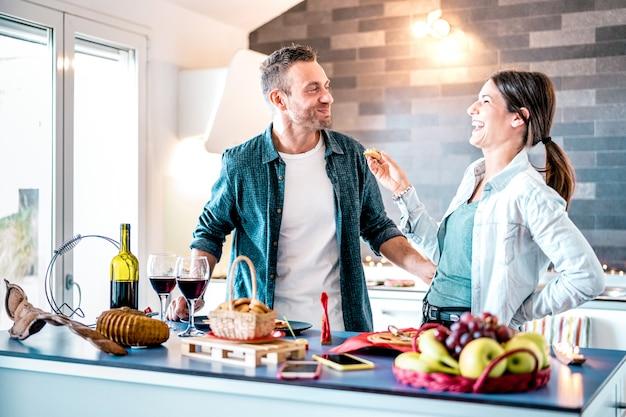 Giovani coppie nell'amore divertendosi alla cucina della casa