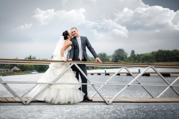 Giovani coppie nell'amore la sposa e lo sposo con un mazzo di fiori in posa su un molo, il giorno del matrimonio in estate. godendo un momento di felicità e amore.