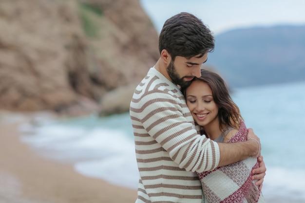 Giovani coppie nell'amore sulla spiaggia belle coppie nel bianco. amanti che si tengono per mano e che abbracciano