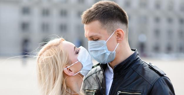 Giovani coppie nelle maschere sulla via della città.