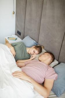 Giovani coppie pacifiche in magliette che fanno un sonnellino a letto