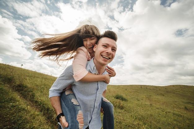 Giovani coppie pazze emozionalmente divertendosi, baciando e abbracciando all'aperto. amore e tenerezza, romanticismo, famiglia, emozioni, divertimento. divertirsi insieme