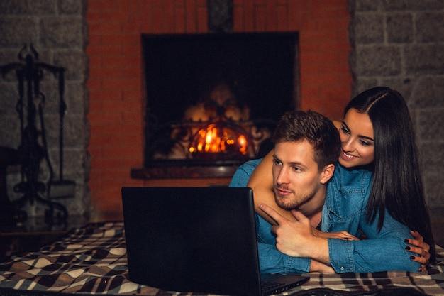 Giovani coppie piacevoli che si trovano sulla coperta e che guardano film sul computer portatile. lo abbraccia da sopra e dietro. sono vicino al camino.