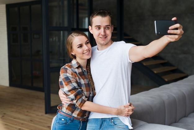 Giovani coppie positive che prendono selfie nella sala a casa