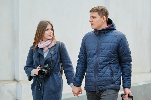 Giovani coppie positive di giovani uomini e donne blogger in città con la macchina fotografica