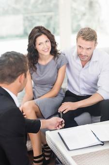 Giovani coppie pronte a comprare nuova casa che interagisce con l'agente immobiliare