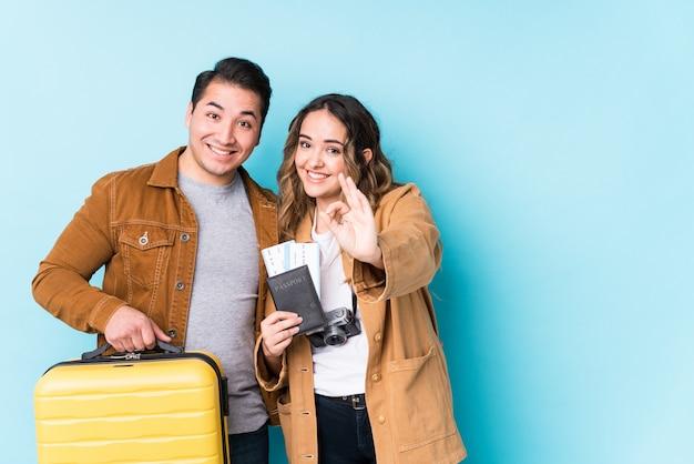 Giovani coppie pronte per un viaggio allegro e sicuro che mostra gesto giusto