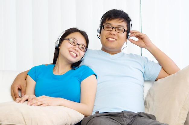 Giovani coppie rilassate con le cuffie che ascoltano musica