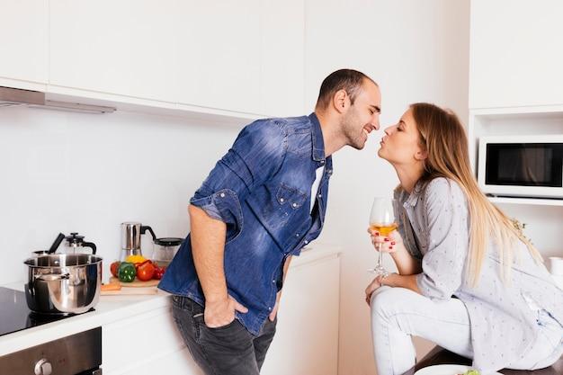 Giovani coppie romantiche che baciano in cucina
