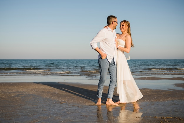 Giovani coppie romantiche che se lo esaminano che si leva in piedi vicino al mare alla spiaggia