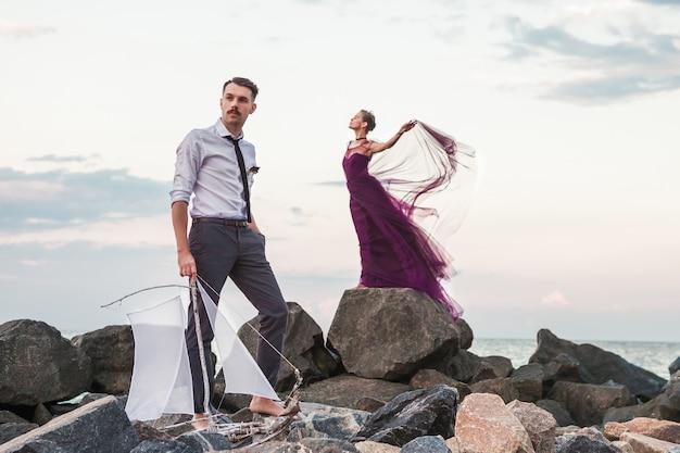 Giovani coppie romantiche che si rilassano sulla spiaggia che guarda il tramonto