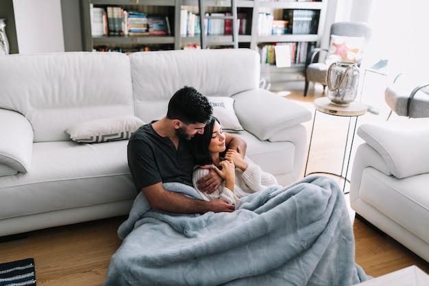 Giovani coppie romantiche che si siedono vicino al sofà in coperta a casa
