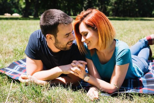 Giovani coppie romantiche che si tengono le mani che si trovano sulla coperta nel parco