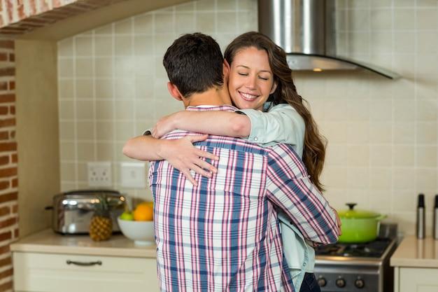 Giovani coppie romantiche che stringono a sé l'un l'altro in cucina