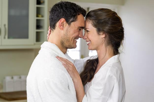 Giovani coppie romantiche in accappatoio che si stringono a sé in cucina